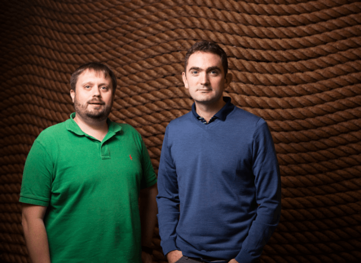Bearded man wearing green polo shirt standing beside clean-shaven man wearing blue jumper and shirt, against brown rope background.