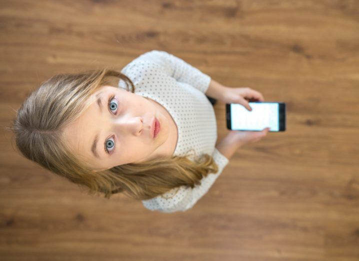Little girl with blue eyes holding smartphone.