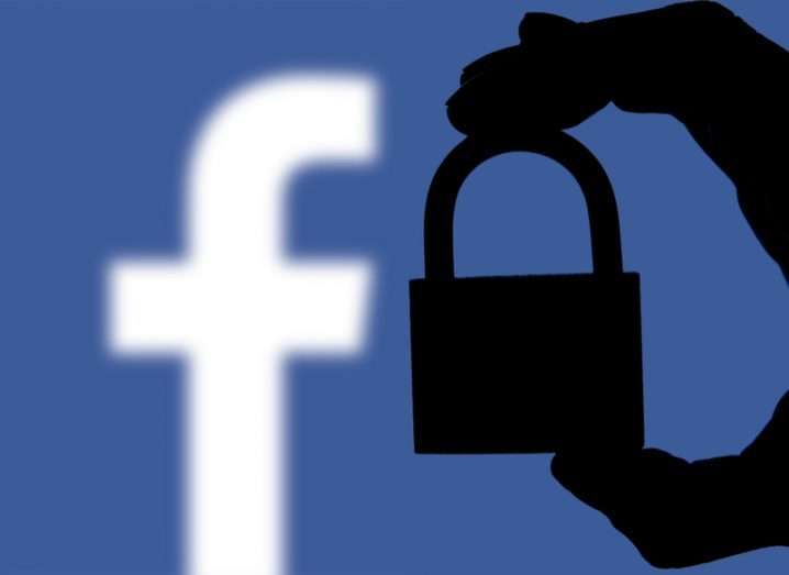 A hand holds a padlock in front of the Facebook logo.