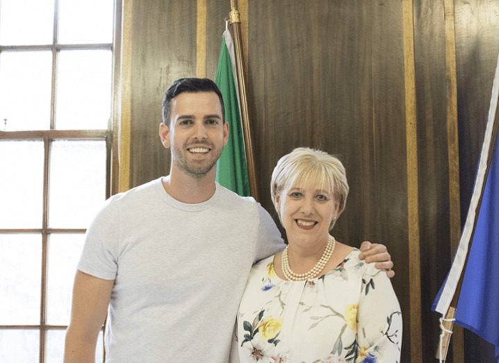Man in white t-shirt stands beside woman in floral blouse in Irish government building.