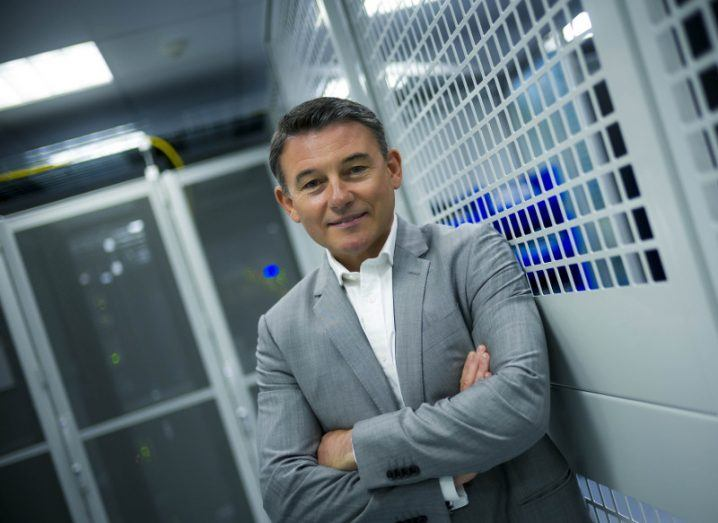 Man in grey suit pictured standing in data centre.