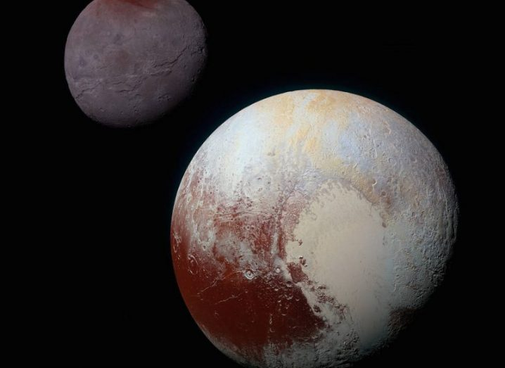 An image of Pluto with its largest moon, Charon to the left of it.