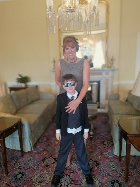 red-haired woman with a protective arm over her young son, who is wearing a suit and sunglasses, standing in a well-furnished room.