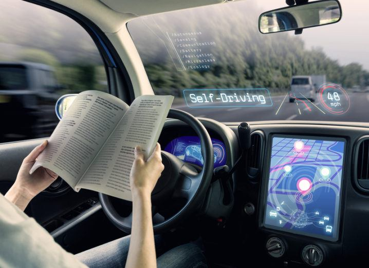 Futuristic image of person reading a magazine while self-driving car takes them on a journey.