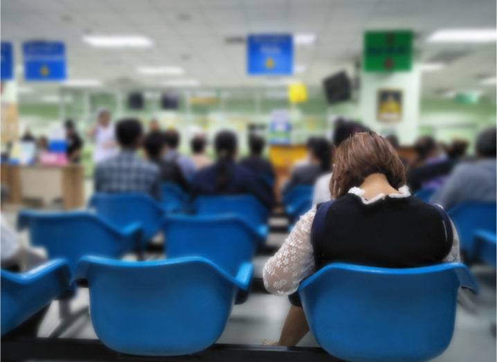 The back of a woman seated in a row of blue chairs as she waits in an NHS accident and emergency ward.