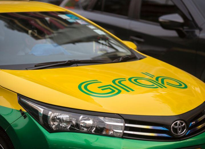 A yellow and green car branded with the Grab logo.