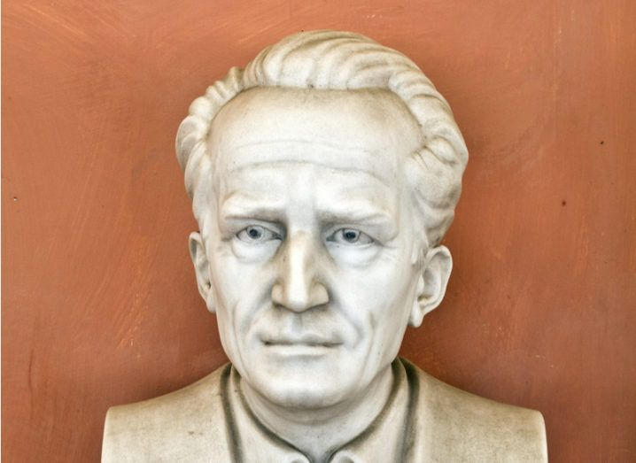 all-white bust sculpture of middle-aged man against orange wall.
