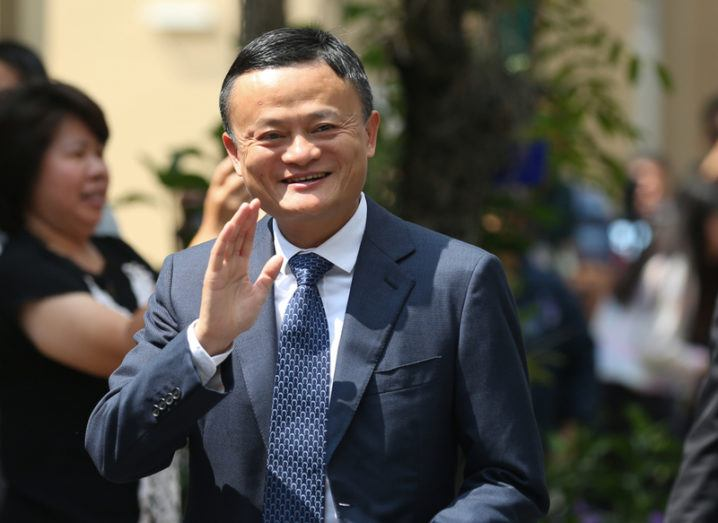 Alibaba chair Jack Ma, smiling and waving, wearing a suit.