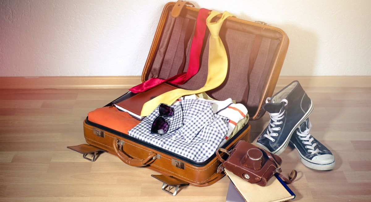 An open suitcase with shirts, ties and shoes strewn around it.