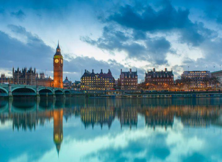 UK Houses of Parliament at sunset, reflected in the River Thames, London.