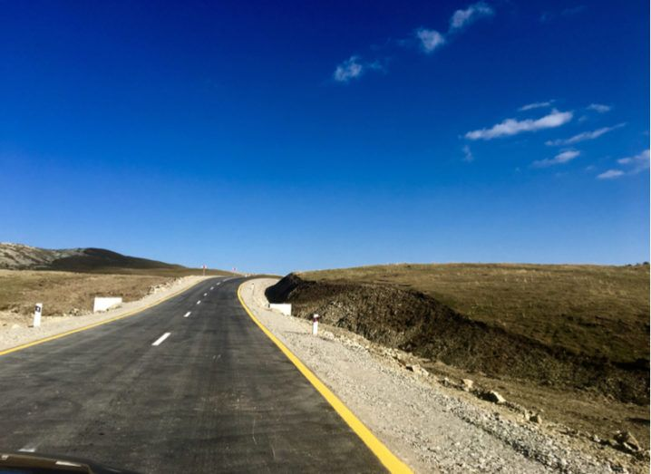 A desolate highway with a sharp turn ahead. Blue skies.
