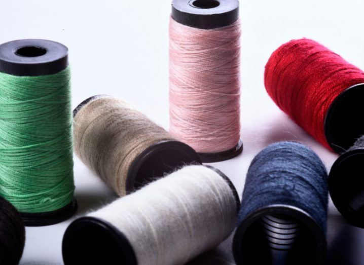 A few spools of colourful cotton thread on a flat surface.