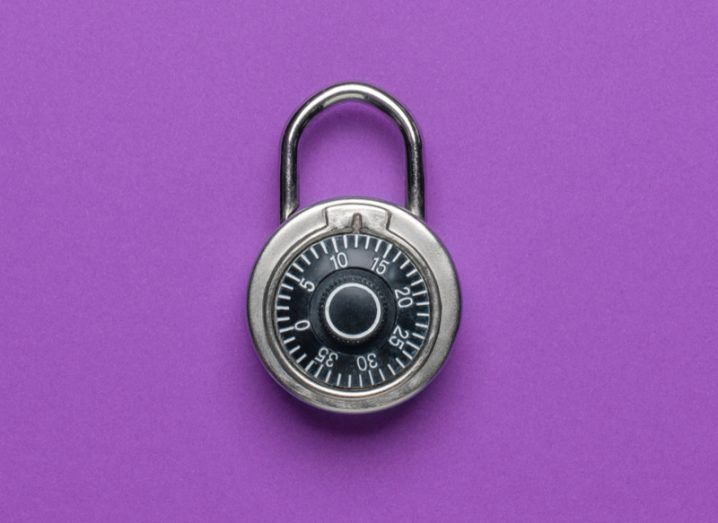 A black combination lock resting on a rich purple background.