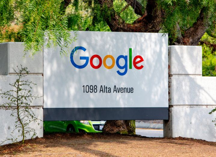 A white sign outside Google headquarters in Silicon Valley, with trees in the background.