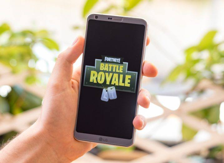 A mobile phone showing the Fortnite Battle Royale game logo with bright lights in the background.