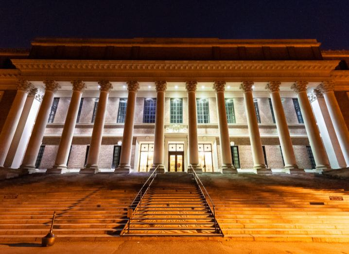 The Widener Library at Harvard University lit up at night. A massive building with many Greek-style columns.