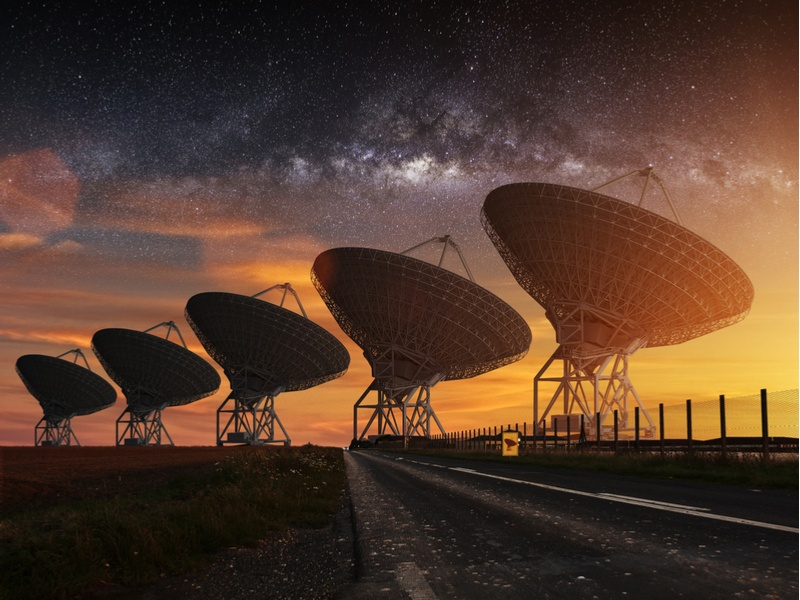 A row of radio satellites in New Mexico at sunset.