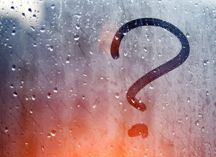 Soft focus view through a glass pane where someone has drawn a question mark in the condensation and raindrops.