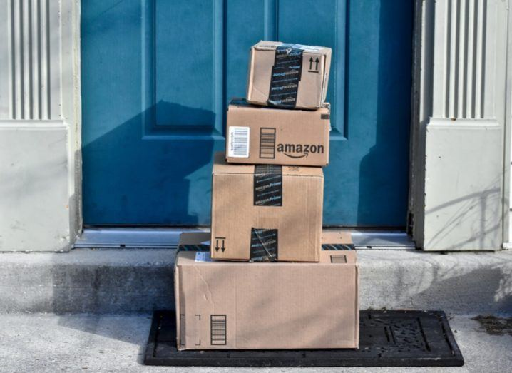A pile of packages from Amazon outside a blue front door.