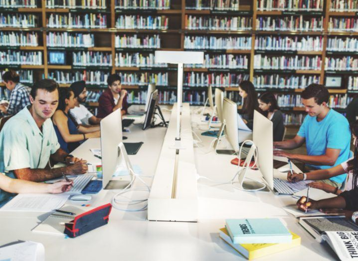 A diverse group of people using computers in a library.
