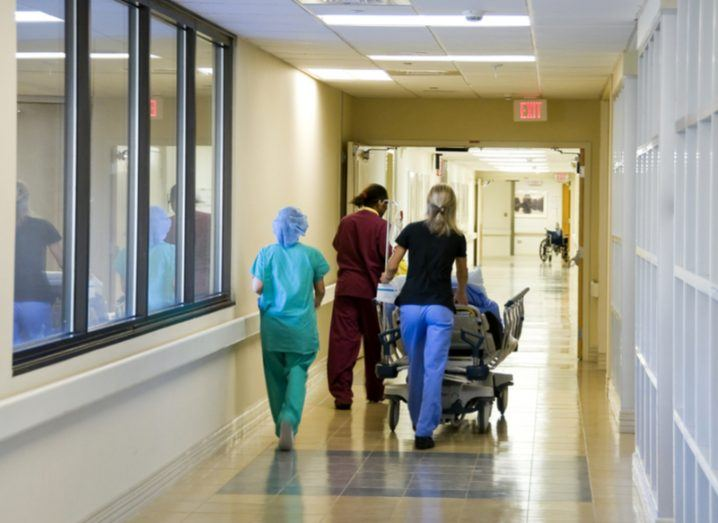 Medical professionals in scrubs walk down a yellow hospital corridor.
