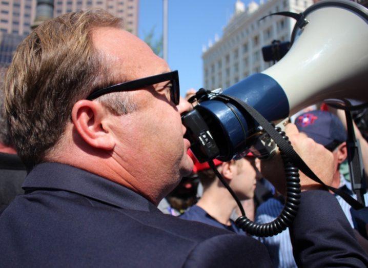 Alex Jones using a megaphone at a protest.