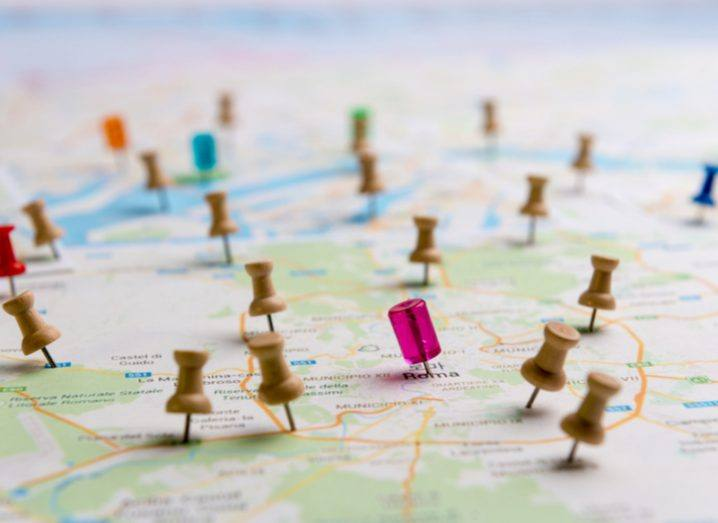 A map with colourful drawing pins stuck in it in various locations.