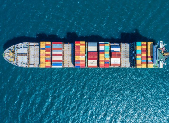 aerial view of ship carrying colourful cargo of shipping containers, sailing on a dark blue sea.