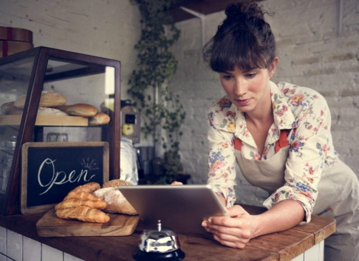 Woman in an independent bakery viewing business documents on her iPad.