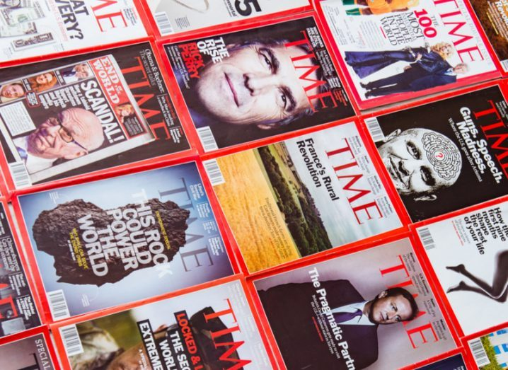 Numerous issues of Time Magazine spread out on a flat surface.