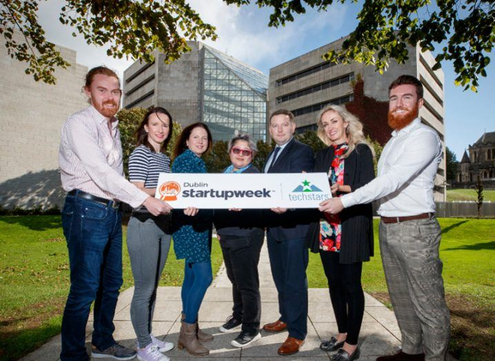 Four women and three men hold a Startup Week Dublin sign in front of Dublin City Council offices.