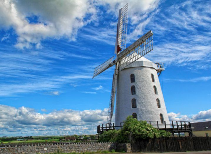 A white windmill stands before a vivid blue sky with clouds.