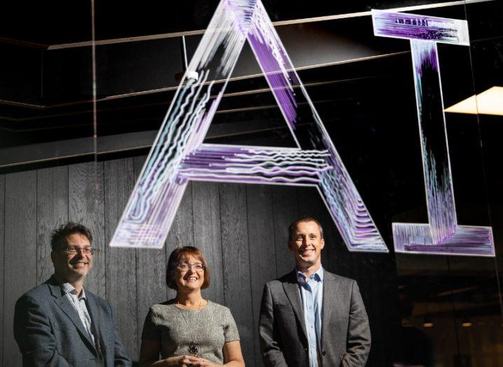Two men and a woman stand under a purple neon sign emblazoned with the words AI.