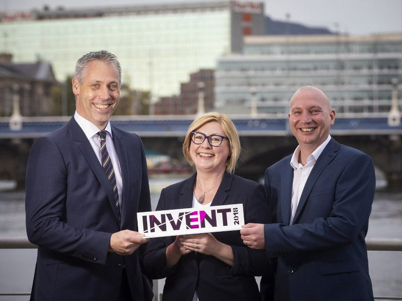 A woman stands between two men on Belfast's waterfront holding an Invent award.