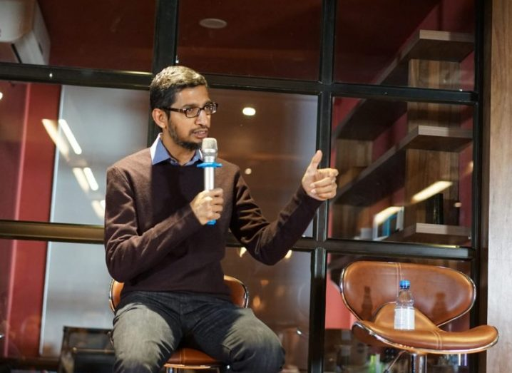 Google CEO Sundar Pichai wearing a brown jumper, speaking into a microphone at a panel discussion.
