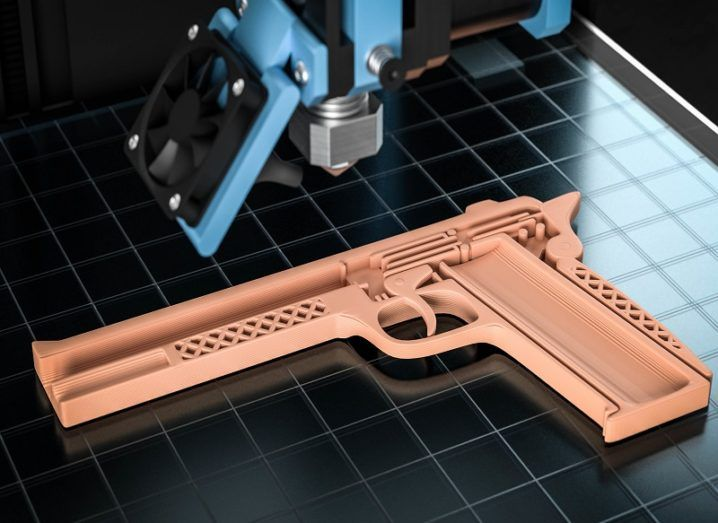 A beige gun-shaped 3D-printed object being printed.