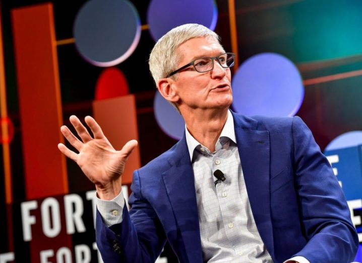 Apple CEO Tim Cook gesticulating at a talk, wearing a navy suit and light grey shirt.