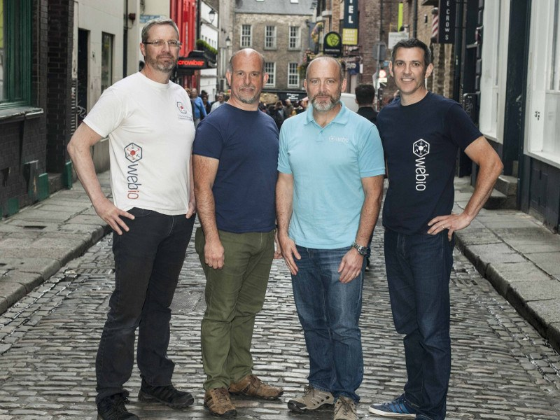 Four men in t-shirts stand on a cobbled street in Dublin.