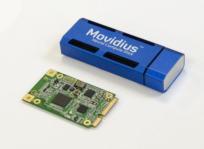 An AI at the edge computer processing board next to a blue USB key labelled 'Movidius Neural Compute Stick'.