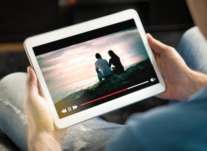 Over-the-shoulder view of a man watching video of a couple on the beach on his tablet.