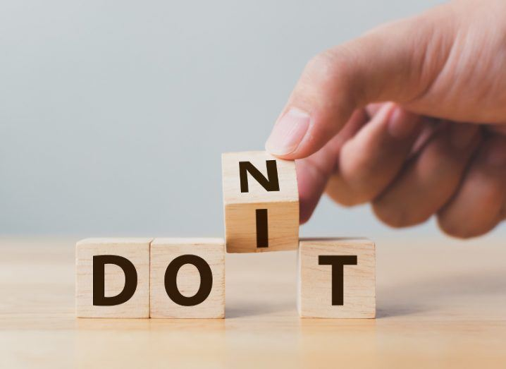 A hand ready to place one more wooden block in a row to spell out either 'Don't' or 'Do it' depending on the placement.