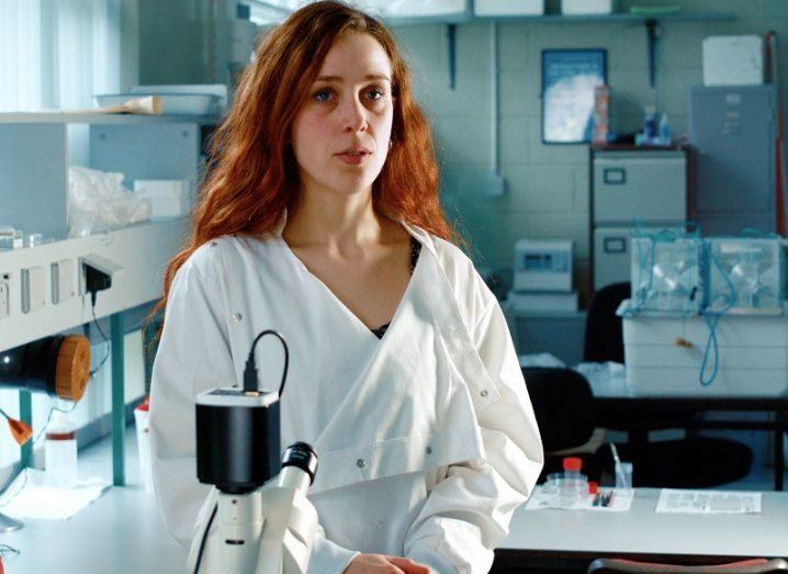 Alina Madita Wieczorek standing in front of a microscope wearing a white lab coat.