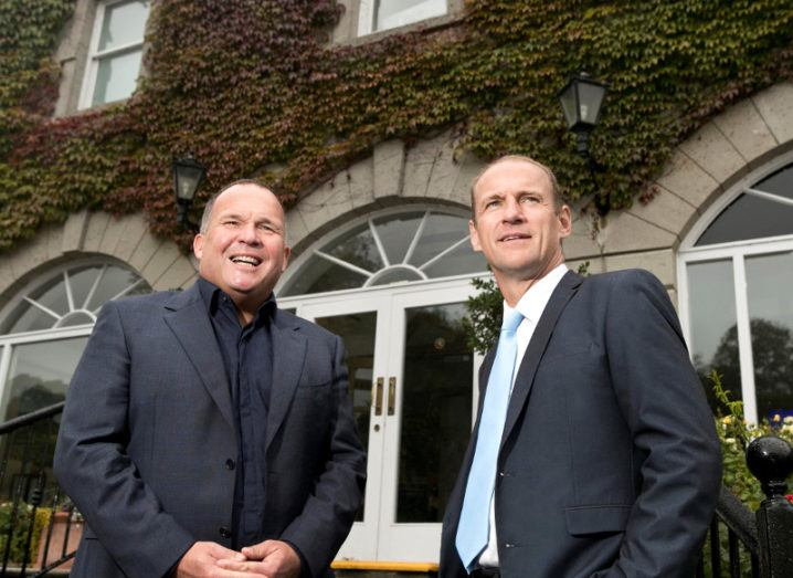 Two men in suits standing before an ivy-covered building.