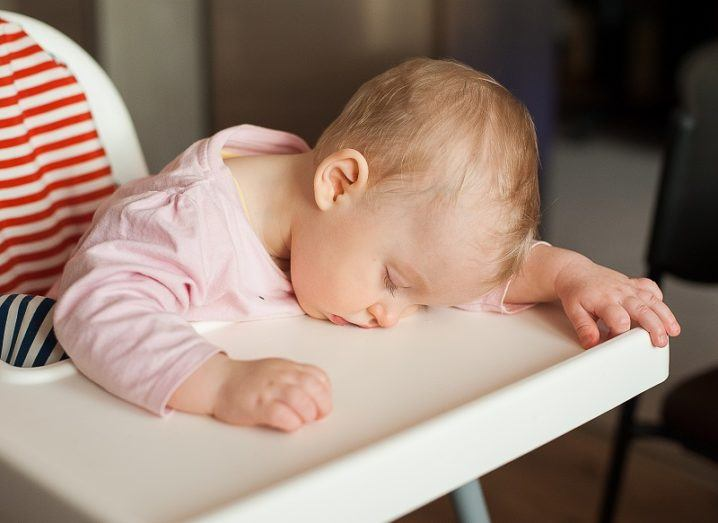 Baby in a pink onesie falling asleep on a high chair.