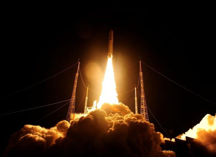 The Ariane 5 rocket taking off at night time, releasing a bright, orange flame.
