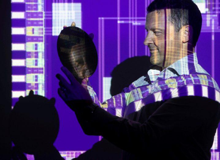 Man holding a silicon wafer with purple screen projected on him.