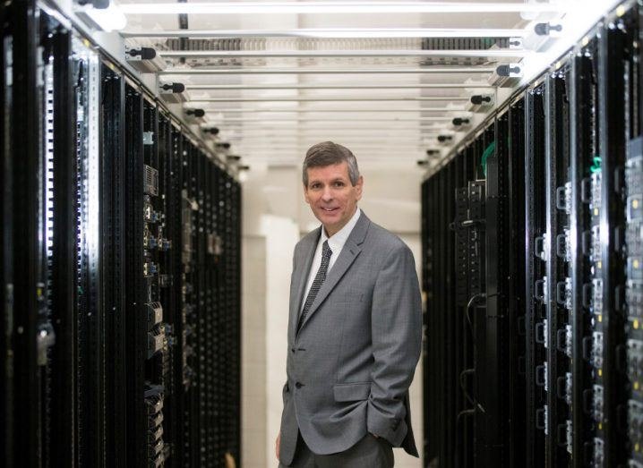 Man in suit stands in data centre hall.