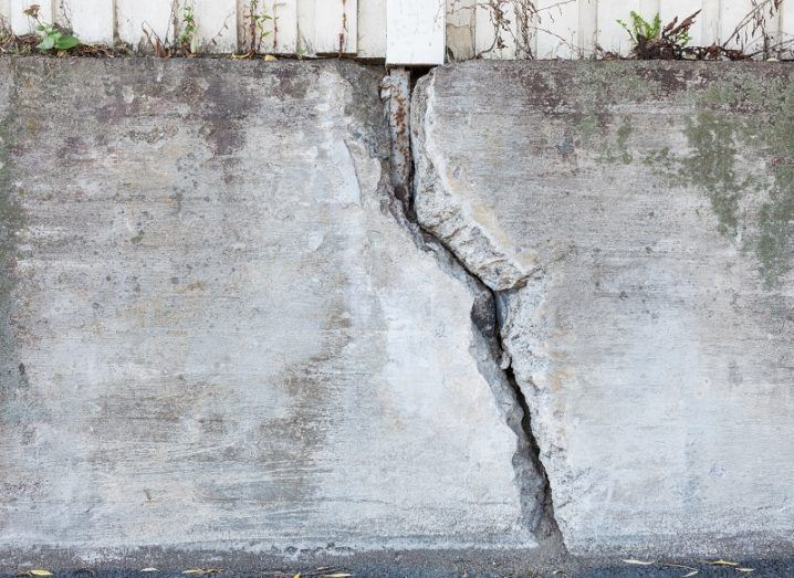 Big crack in an old, outdoor concrete wall.