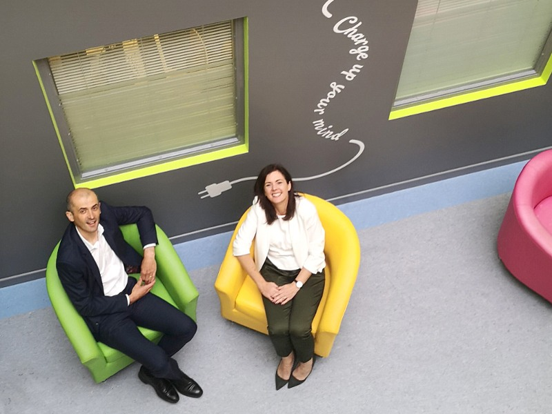High-angle shot of a man sitting on a green chair and a woman sitting on a yellow chair.