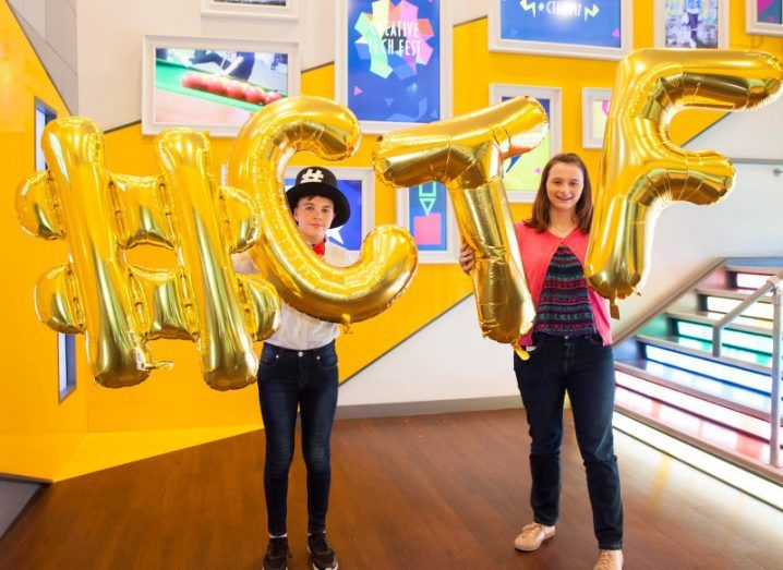 A young boy and a young girl stand in a colourfully decorated stairway holding gold foil balloons that spell out '#CTF'.